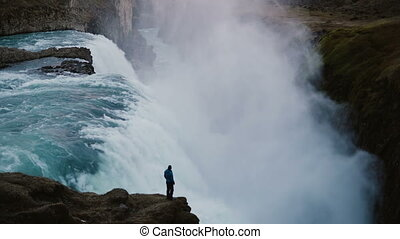 Beautiful view of the man standing on the edge of the rock and looking on the Gullfoss waterfall in Iceland.