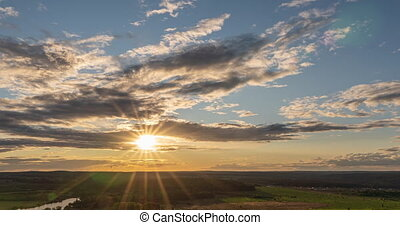 Beautiful view of the wild field during sunset, time lapse, clouds of different levels move to the camera, beautiful sunset.