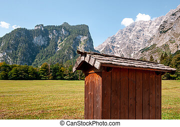 Beautiful view of traditional wooden boat house at the shores of famous Lake Obersee in scenic Nationalpark Berchtesgadener Land