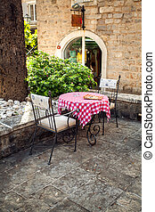 two chairs and table on summer terrace of old restaurant - ...