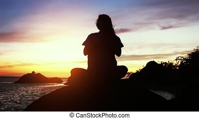 Beautiful view of woman doing yoga, meditating near the sea on the rock on a sunset background. slow motion.
