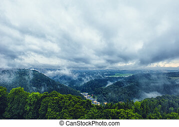 Beautiful view on a small town in the mountains with a dramatic cloudy sky.
