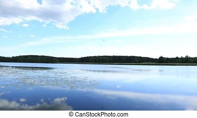 Beautiful view over wonderful nature landscape. Lake water surface and blue sky with white clouds. Beautiful nature landscape background.