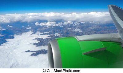 Beautiful view through airplane window, airplane flying above the clouds and mountains