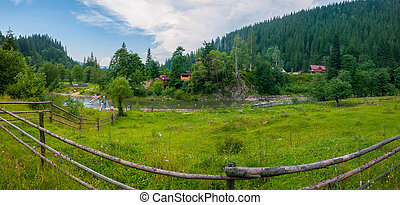 Beautiful views of the mountainous terrain with the current river between the low banks with green grass on one side and trees and houses on the other.