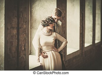 Beautiful vintage style couple standing near window