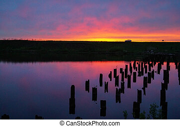 Beautiful violet-blue sunset on a small river wooden posts in the water
