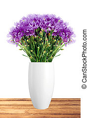 Beautiful violet flowers in vase on wooden table over white