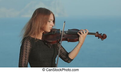 Beautiful violinist in tracery dress plays on a rock by the sea