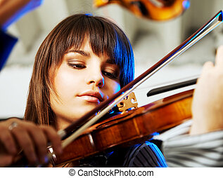 portrait of a beautiful young violinist playing indoors