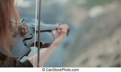 Beautiful violinist plays outdoors on her a musical...