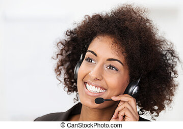 Beautiful vivacious young African American client services, call centre operator or receptionist smiling a warm friendly natural smile as she listens to a client speaking on her headset