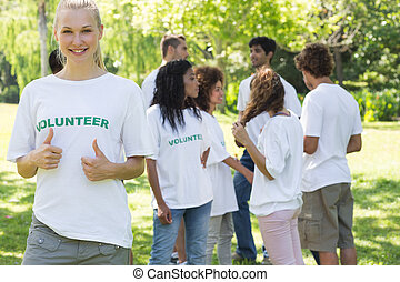 Beautiful female volunteer gesturing thumbs up with friends disucssing in background