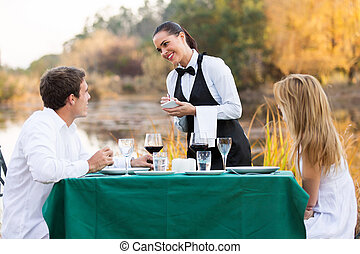 beautiful waitress taking order from customer outdoors