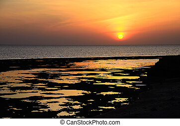 sunrise on sea with reflections on the beach