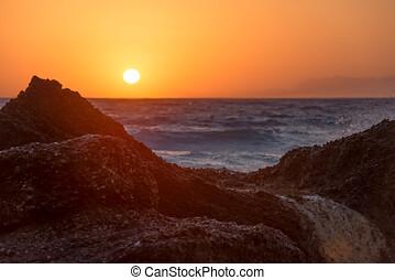 Beautiful warm sunset light glowing over a rocky tropical beach