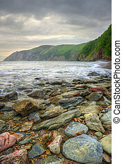 Lovely image of sunrise over incoming tide with rocky foreground and cliffs in background