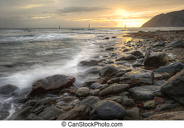 Beautiful warm vibrant sunrise over ocean with cliffs and rocks