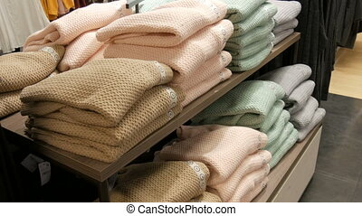 Beautiful warm women's knit sweaters of light color folded in a row on a shelf in clothing store