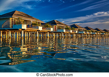 Beautiful water villas on the vibrant blue sea during sunset