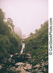 beautiful waterfall and people walking on rocks in Indian Himalayas, Dharamsala, Baksu