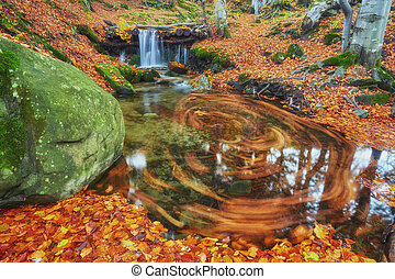 Beautiful waterfall at mountain river in colorful autumn forest with red and orange leaves at sunset.