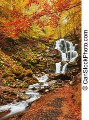 Beautiful waterfall at mountain river in colorful autumn...