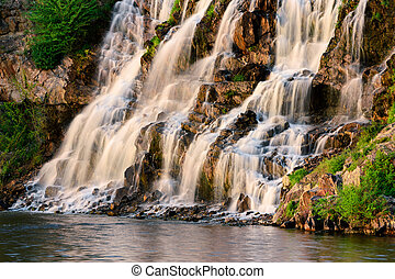 Beautiful waterfall at sunset in the rays of the setting sun II