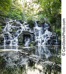 Beautiful waterfall cascades over rocks in lush forest ...