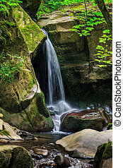 waterfall comes out of a huge stone in forest - beautiful...