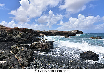 Beautiful Waves Crashing on Black Sand Stone Beach in Aruba