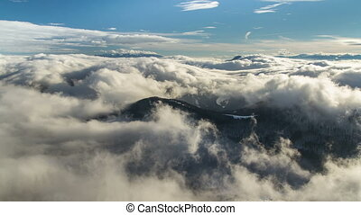 Beautiful waves of low clouds flows in winter mountains time lapse