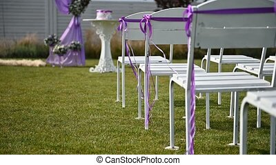 Beautiful Wedding Arch Standing near Chairs and Wall of Green Plants. Decorations for Wedding Ceremony