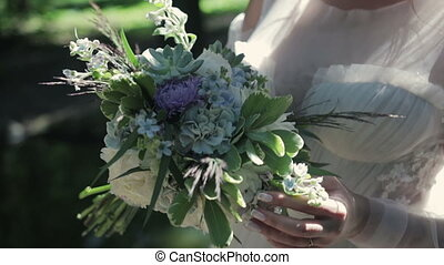 Beautiful wedding bouquet of flowers in hands of the bride