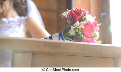 Beautiful wedding bouquet of flowers lie on wooden table.