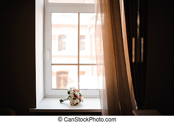 Beautiful wedding bouquet of flowers on the window sill