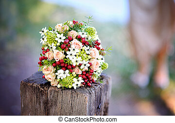 beautiful wedding bouquet with red flowers lying on a tree stump