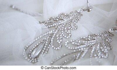 Beautiful wedding bride earrings on the veil closeup