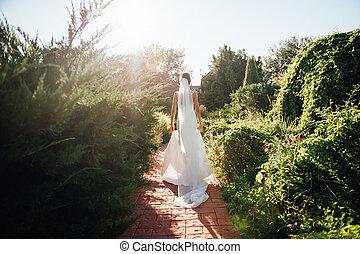 Beautiful wedding bride running in the garden