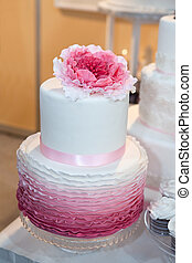 Beautiful wedding cake with pink flower on top