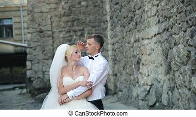Beautiful wedding couple at a wall of stone