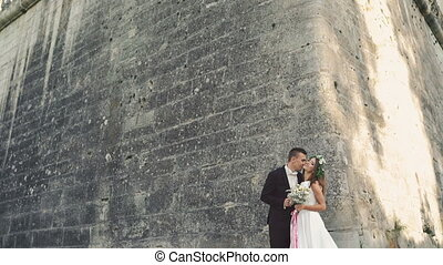 Beautiful wedding couple embracing near the castle wall 4K