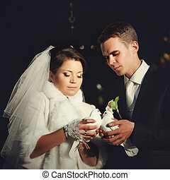Beautiful wedding couple holds white pigeons behind each other