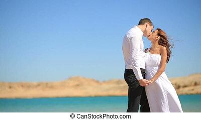 Beautiful wedding couple kissing on sea background. Honeymoon in Egypt.