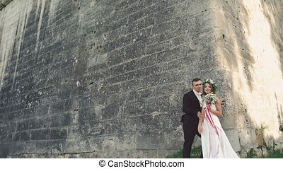 Beautiful wedding couple near the castle kissing and smiling. 4K