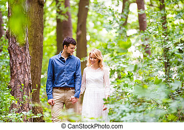 Beautiful wedding couple on a walk in forest, holding hands.