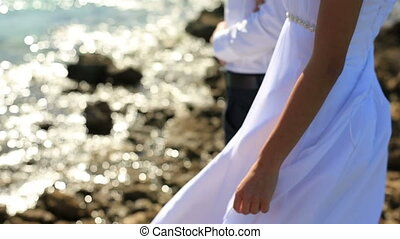 Beautiful wedding couple on the coast.  Long dark hair fluttering in the wind. Sea background.