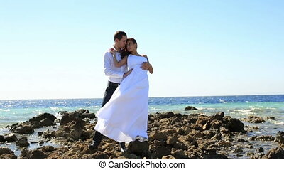 Beautiful wedding couple on the stoned beach . Honeymoon in Egypt. Sea background