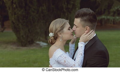 Beautiful wedding couple standing on the green glade and sensually hugging
