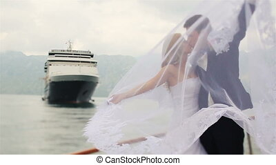 Beautiful wedding couple tenderly kissing on the yacht with the mountains and sea on background